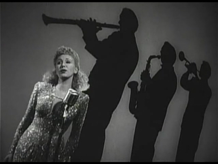 Canted angle shot. Singer in foreground and silhouettes of horn players in background. Image appears tilted.