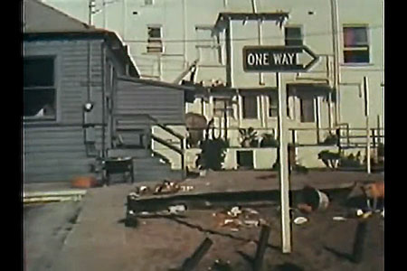 Shot of rundown house with one-way sign in foreground.