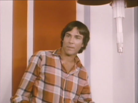 Man in orange plaid shirt stands against orange and white background. His face and figure are brightly lit, with almost no shadowing.