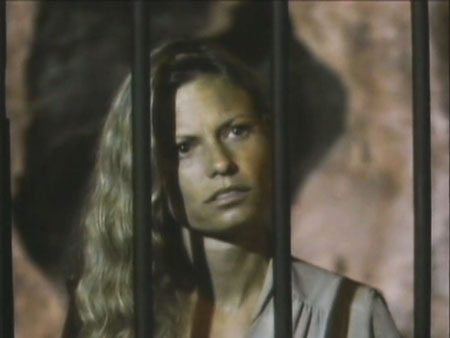 Woman's head and shoulders behind bars. Bars form shadows on her face.