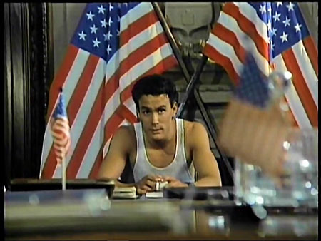 Medium shot. Figure seated at desk with American flags in background.